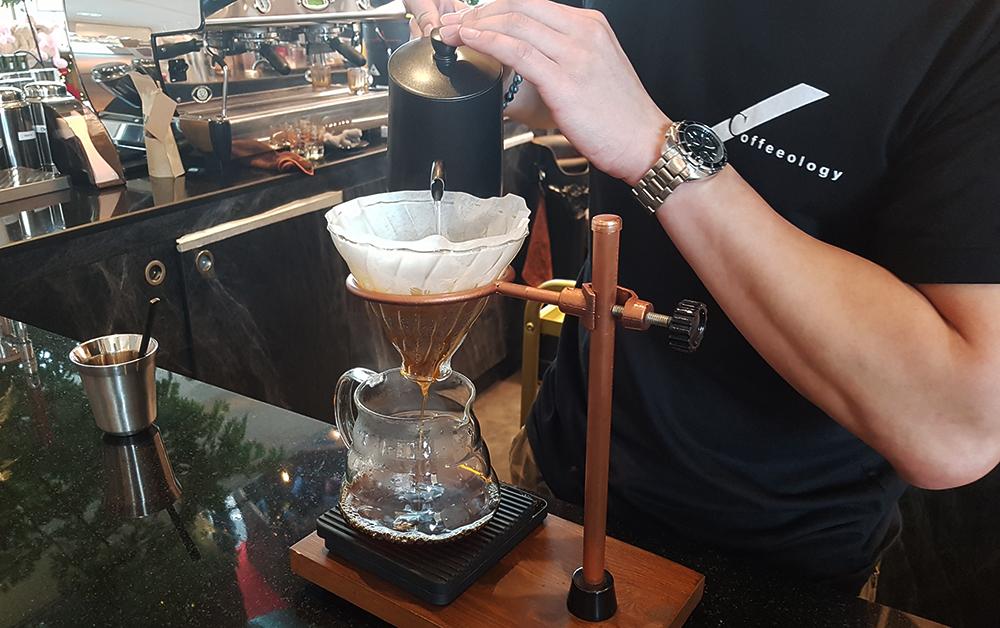 בריסטה מכין קפה פילטר ב-Hario V60 בבית קפה של הגל השלישי בבנגקוק