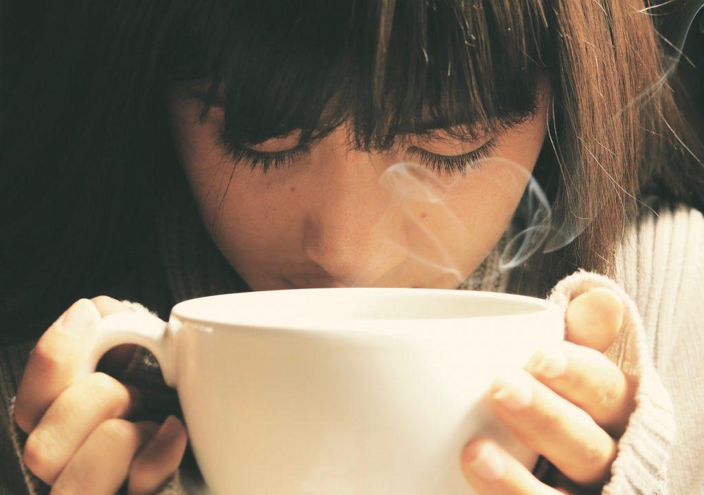 אשה שותה כוס קפה גדולה. צילום: Pixabay