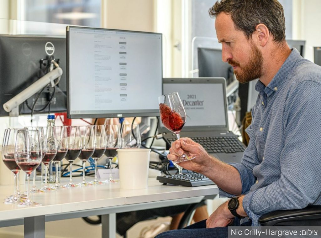 שופט טועם יין אדום בתחרות DWWA של מגזין דיקנטר 2021. צילום: Nic Crilly-Hargrave