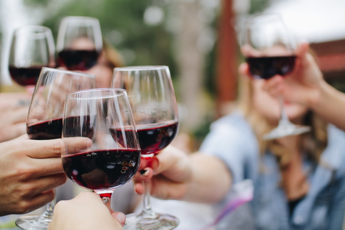 קבוצה עושה לחיים עם כוסות יין אדום. צילום: Kelsey Knight