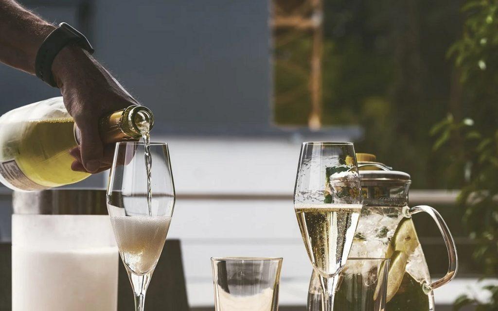 מוזג יין לבן מבעבע לכוסות שמפניה. צילום: NickyPe